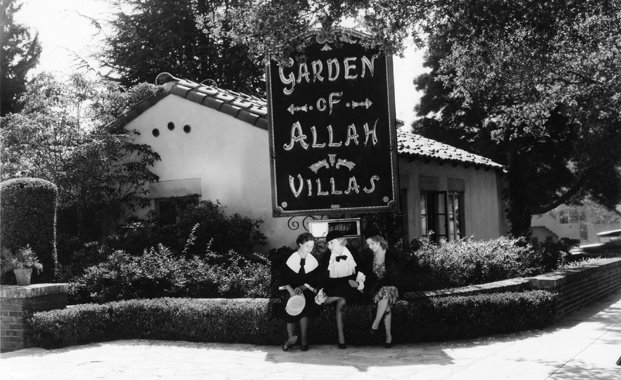 Three women pose for a publicity photo in front of the Garden of Allah sign, with Villa 1 in the background