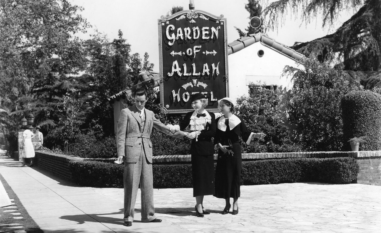 A man and two women pose for a publicity shot of the hotel sign near Villa 19
