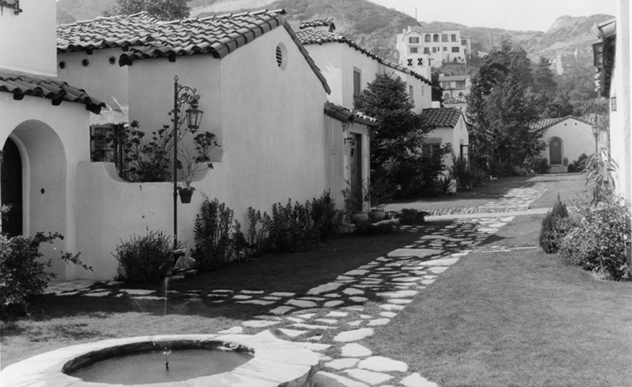 A fountain and pathway heading north past villas 6 through 2, with the entrance of Villa 1 straight ahead